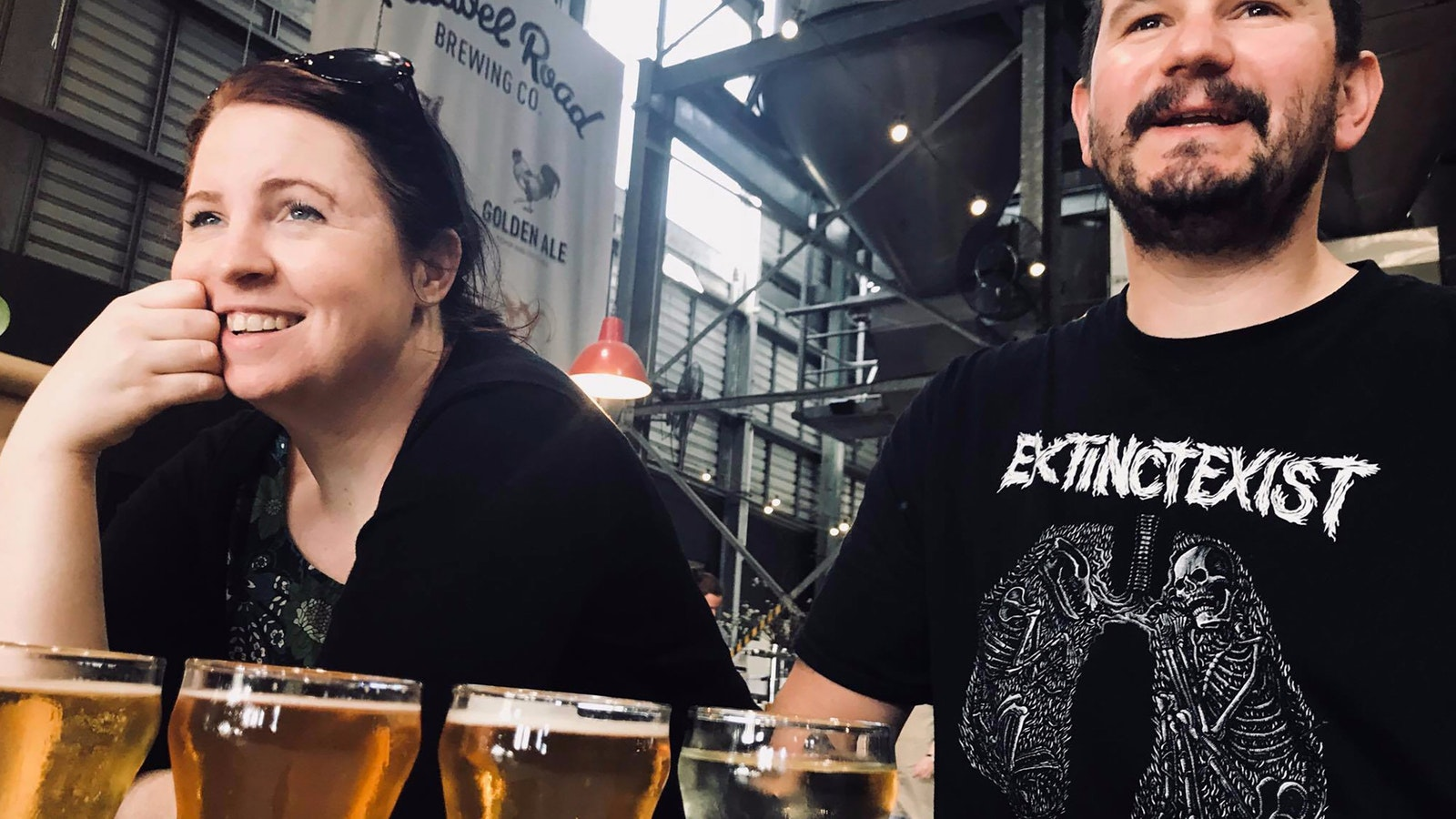 2 people laughing over a beer paddle in a brewery