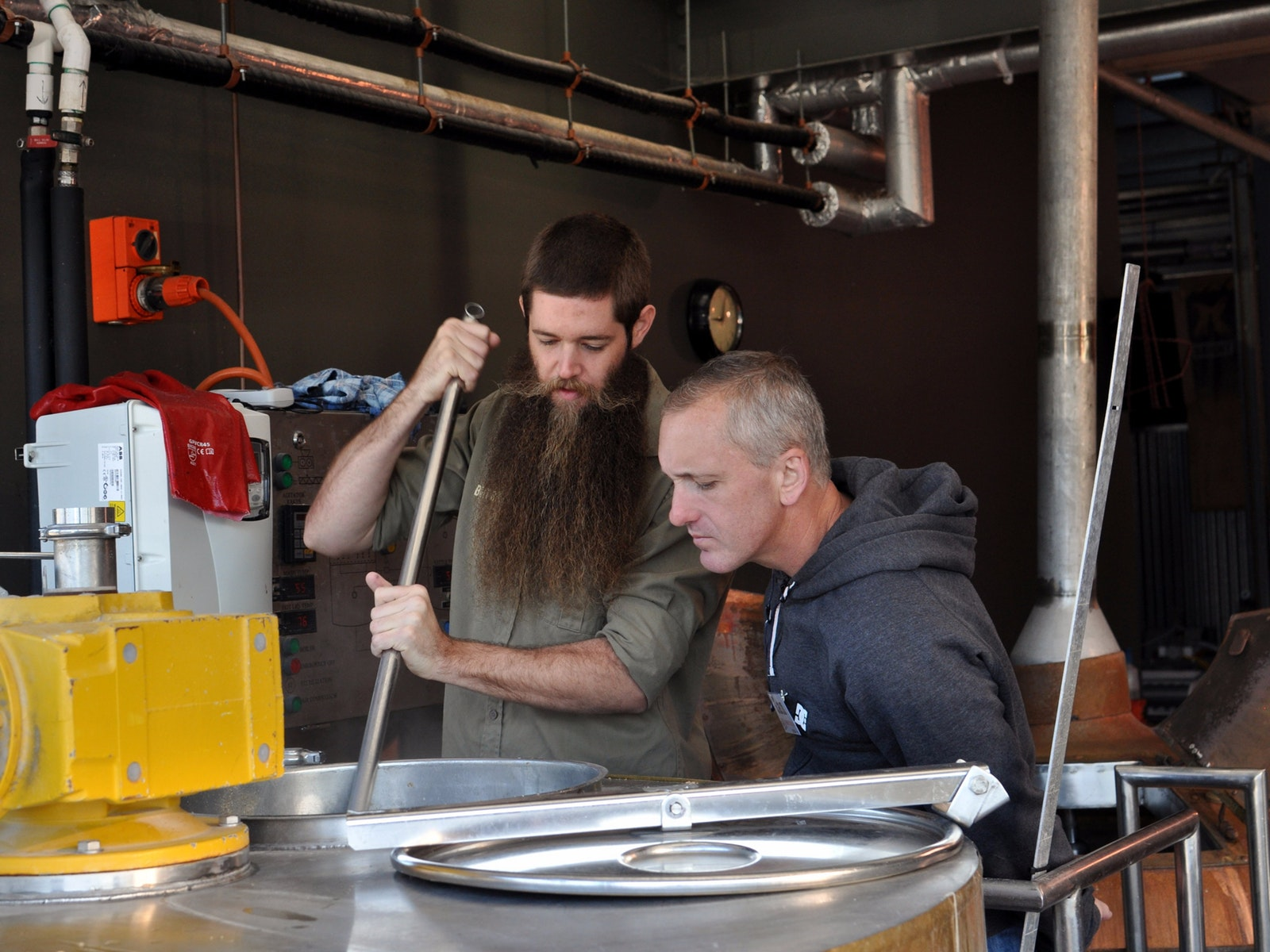 A brewer instructs a man in brewing