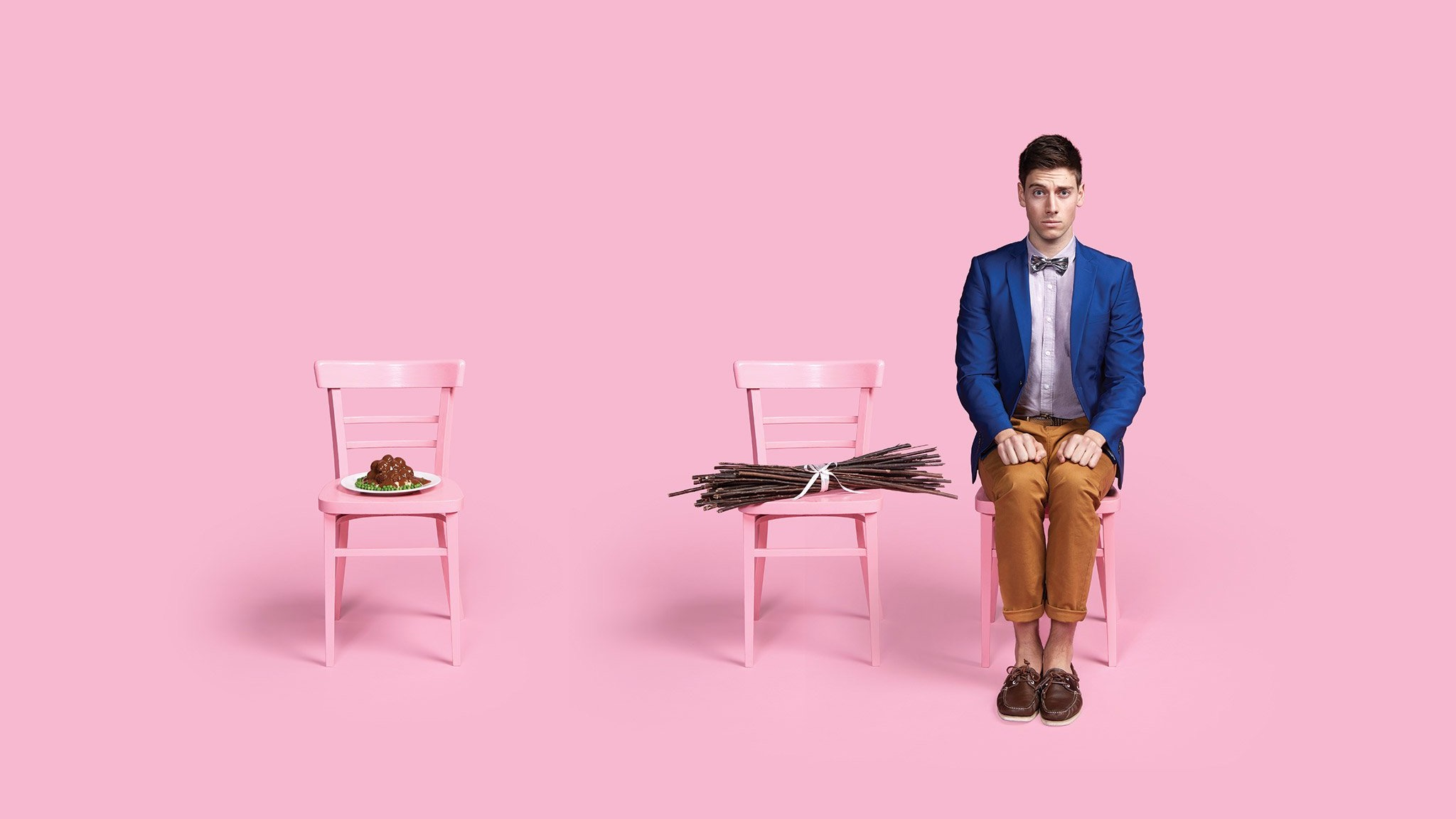 on 3 pink chairs against a pink background sits Irish faggots, a faggot of sticks and a man