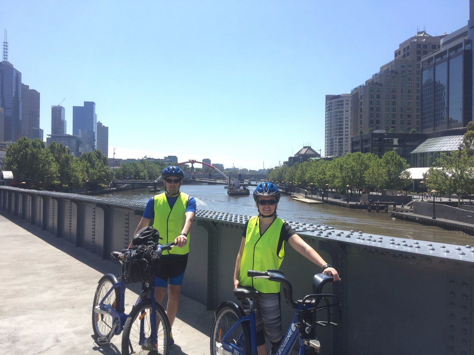 two riders on bridge overlooking Melbourne