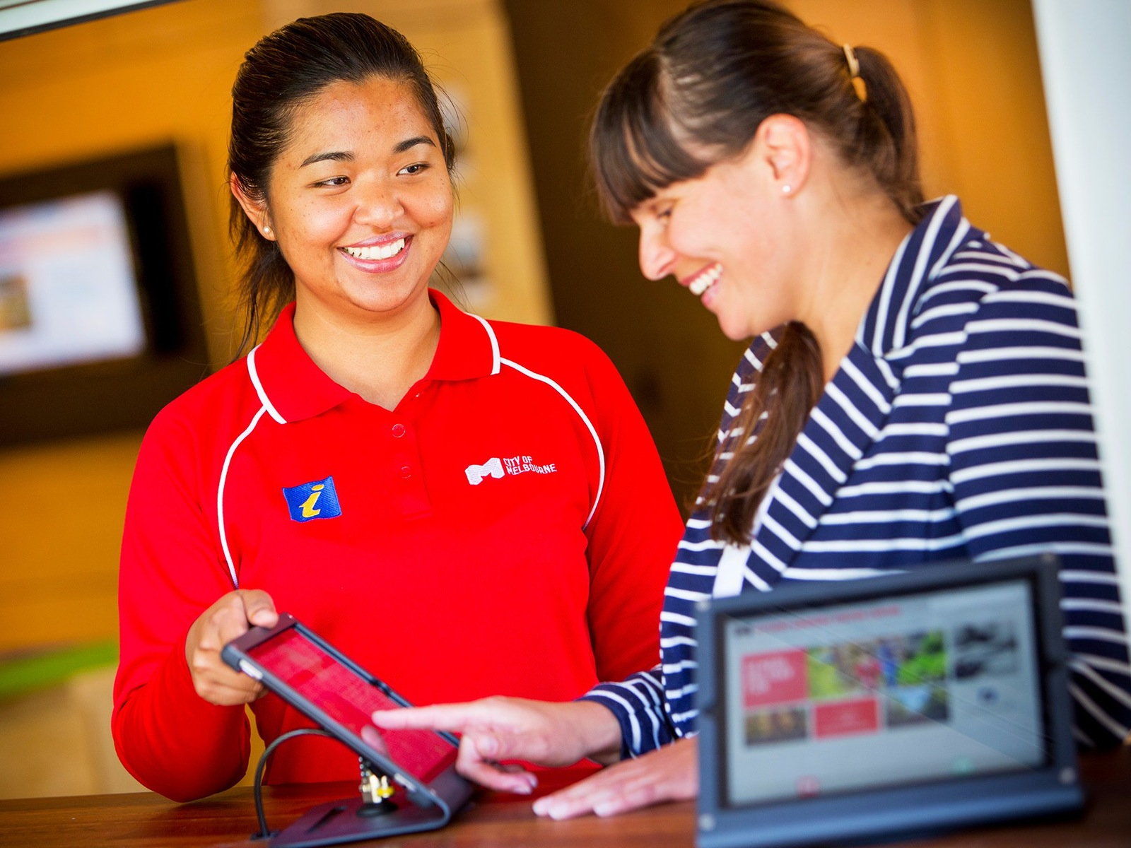 A smiling City of Melbourne volunteer in a red shirt assisting a female visitor to use an ipad