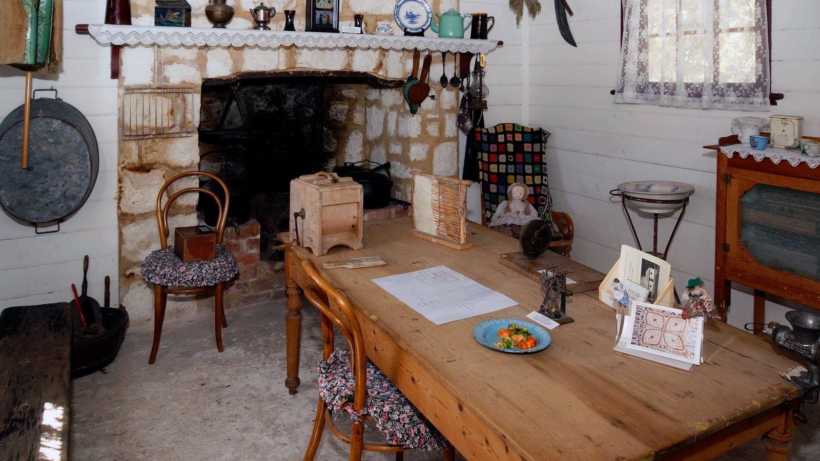 Living room in Watts Cottage with wooden table, chairs and old fireplace with  items used in 1870s