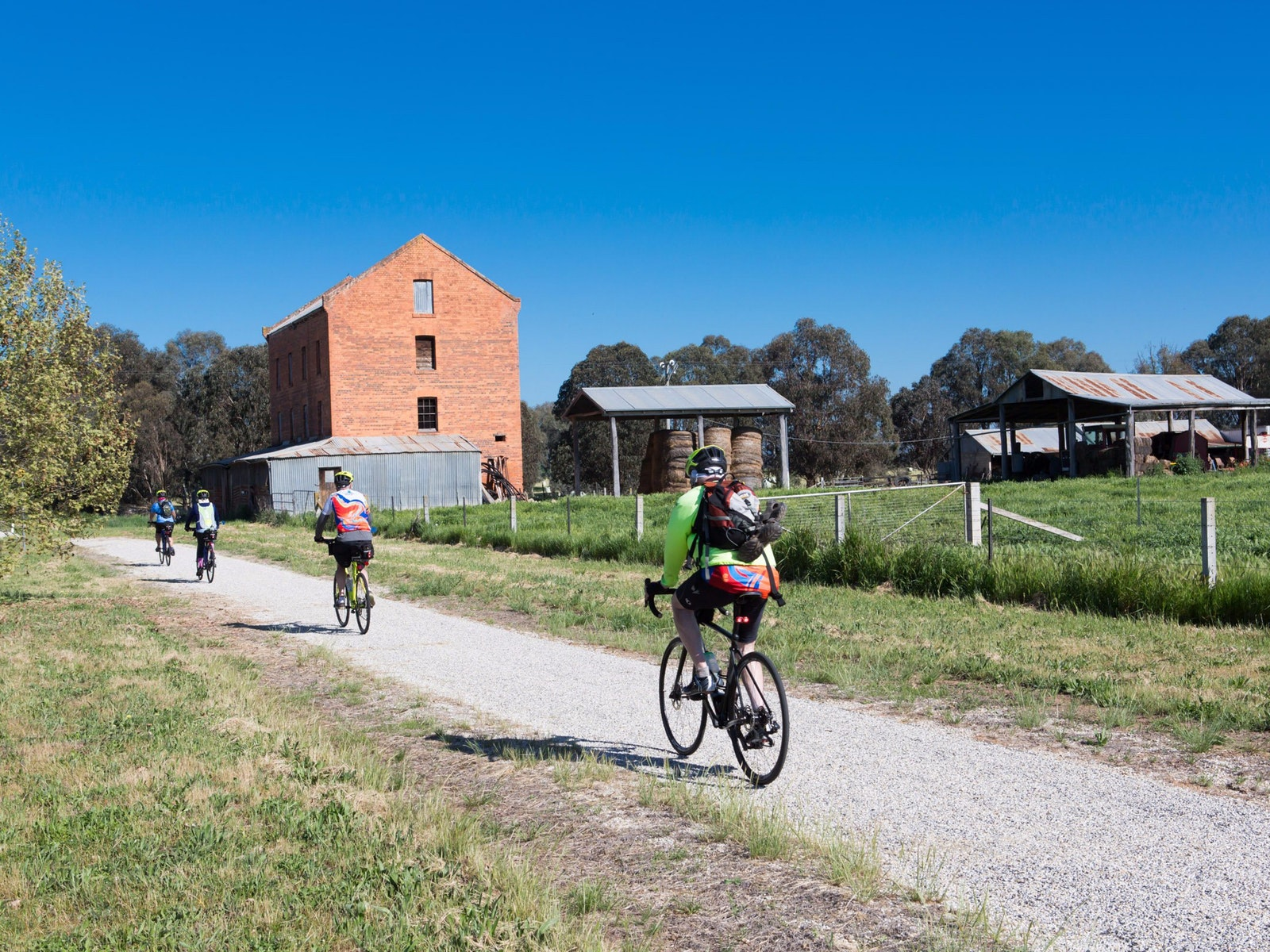 four cyclists on rail trail passing ruin of old mill and hay sheds