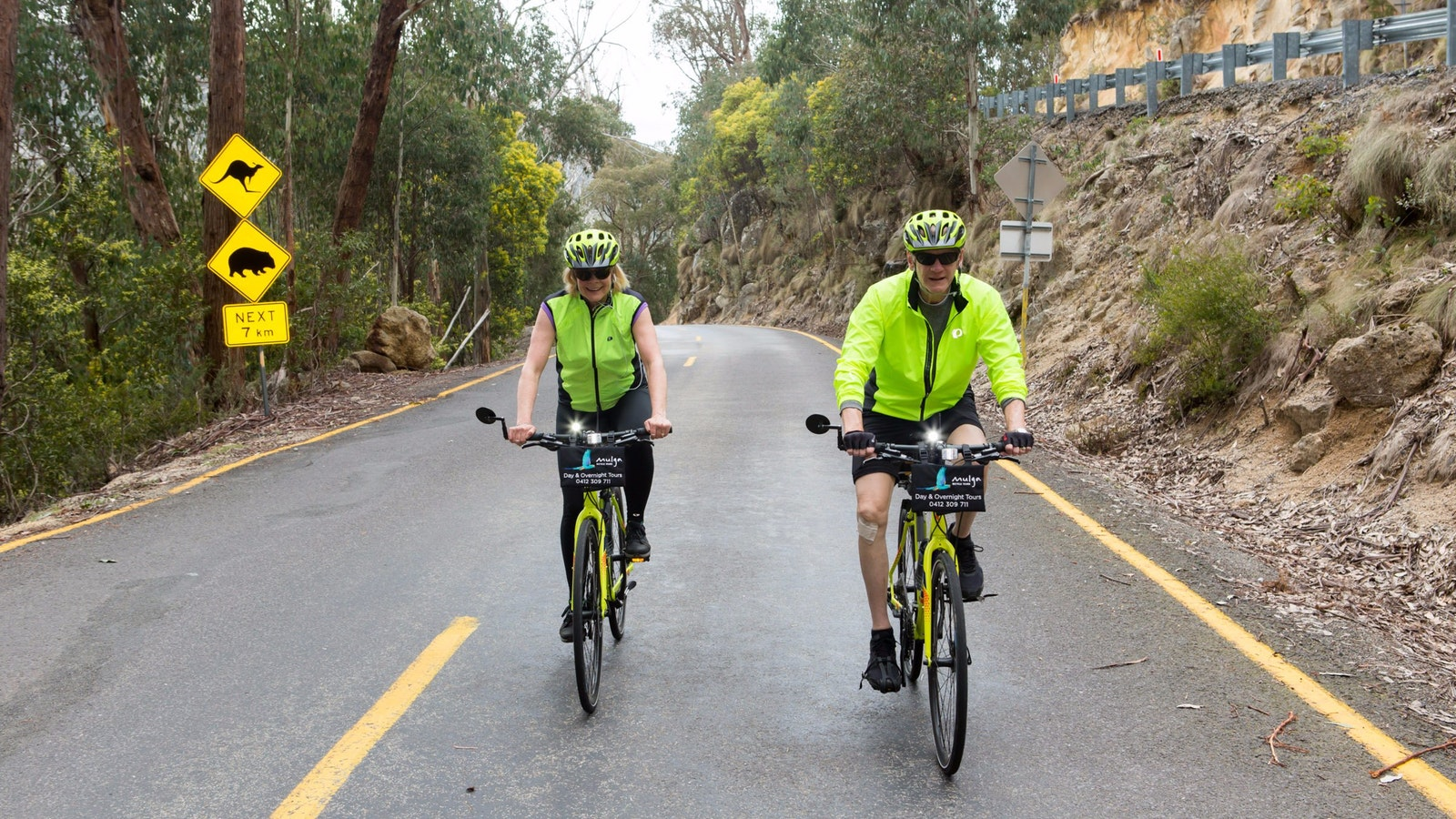 cyclists side by side on road. Kangaroo and Wombat warning signs behind them