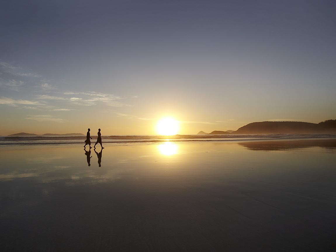 Couple walking along Squeaky Beach at sunset, Gippsland, Victoria, Australia